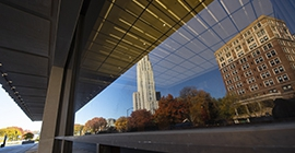 cathedral of learning and student union reflected in nearby window